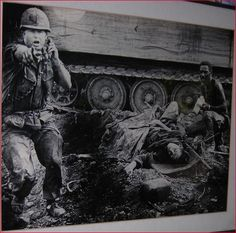 """Photo by Oliver Noonan - near Saigon - Vietnam - 1969. During an ambush by Viet Cong guerrillas, a wounded soldier awaits evacuation. He is attended by a medic as they seek cover beside an armored troop carrier beside an officer who shouts orders."