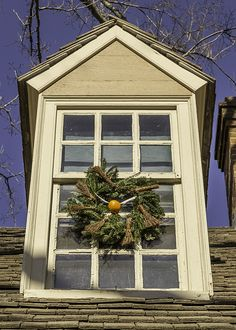 "A wreath with a ""flying orange"" and tiny little brooms adorns a dormer window on a house in Colonial Williamsburg at Christmas."