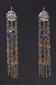 China |  Silver, coral and enamel earrings.  First half of 20th century. China | Propitiatory symbols are embossed in silver and are reproduced in varnish elements recreating a pleasant harmony together. The pendants had also a superstitious function that attracted the gaze of the malevolent spirits and dispel the evil eye | 880,00 €