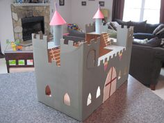Cardboard box castle (side view).  Twine for ladders & working drawbridge.  Windows on all sides.