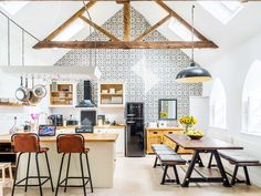 A tiled and lofty kitchen with a modern yet rustic style, picnic table, and industrial light