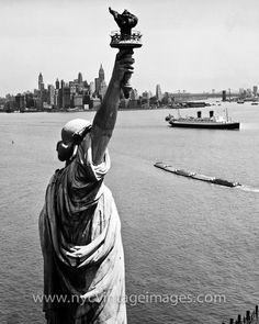 The Statue of Liberty stands at the entrance to New York Harbor, welcoming all to the land of liberty. Looking past her, you can see a string of barges heading into the harbor and an Ocean Liner heading out. Beyond them are the Lower Manhattan Skyline and the East River bridges. Thegolden age of transatlantic sailingwas coming to an end by this time, and the era of jet travel was about to begin.