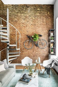 I love this modern industrial apartment. And look at the bike on the wall. What a way to display greenery. It's the industrial NoHo loft apartment of a New York–based private equity analyst.