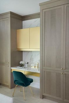 Modern and luxurious kitchen style was used when making this small kitchen desk. Gold cabinets and a teal velvet chair give the desk a fancy look. Kitchen inspiration for small areas looking to maximize space with a kitchen desk. #kitchenideas #kitcheninspiration #kitchendesk #deskideas #workfromhome