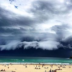 Nature looks like an artwork in this image with the sky as dark as night as the storm creeps up on people sunning themself on a Sydney beach