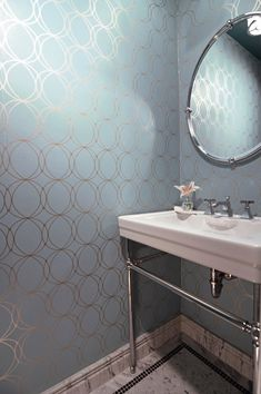 Stunning powder room with Graham and Brown Darcy Wallpaper framing a chrome washstand with porcelain sink below an oval nickel framed mirror over white marble mini hex tiled floors bordered by black mosaic tile.