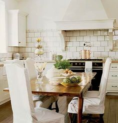 A table in the center of the kitchen instead of an island? If you have the room for one, why not? I also love that gorgeous range hood and tile detail.