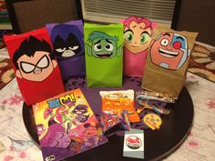 Ideas for Teen Titan goody bags. Got different colored bags from Party City and regular brown from the grocery store. It's easier to just cut their heads as one piece and taped down with double sided tape. We were able to find Teen Titan comics at our awesome comic book store.