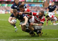 Mark Bennett of Scotland goes over to score his teams 4th try despite a tackle by Michael Leitch (R) of Japan during the 2015 Rugby World Cup Pool B match between Scotland and Japan at Kingsholm Stadium on September 23, 2015 in Gloucester, United Kingdom.  (Photo by Ben Hoskins/Getty Images)