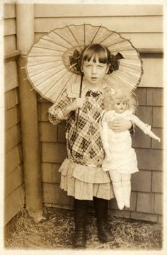 Antique Edwardian photo of a little girl with a parasol and a doll.