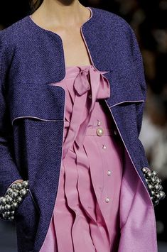 Chanel Spring 2013 - lilac silk dress with pleats and pearl buttons. The collarless  overcoat of navy blue tweed.  Notched front & slightly flared yoke edged with lilac piping.  Lined with the same lilac silk as the dress.  Faux black pearl cuff bracelets on either wrist!  Fab!
