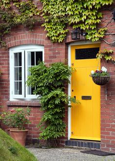 Photo about Yellow front door entrance and old style window of a red brick house or a cottage with hanging flower basket and green ivy. Image of house, building, cottage - 27594647 Exterior Door Colors, Front Door Paint Colors, Painted Front Doors, Exterior Doors, Entry Doors, Entryway, Exterior Paint, Orange Front Doors, Best Front Doors