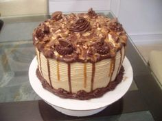 Decadent chocolate cake made with homemade peanut butter frosting and topped with chopped Reese Peanut Butter cups, drizzled with melted Reese Peanut Butter cups and melted caramel that slides down the sides of the cake!