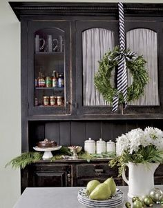 Love the green and white Christmas decor against the distressed grey cabinetry..