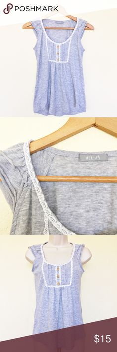 """dELiA*s Lace and Ruffled Tank Top Tank top by dELiA*s. Features white lace on neckline with buttons down center. Ruffles on shoulders of tank. Super cute, great condition! Size M, be sure and check measurements. Armpit to armpit: approx 15 1/2"""". Length of tank: approx 24"""". dELiAs Tops Tank Tops"""