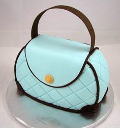 This cake was made from an 8 inch round, with the top and bottom cut off to form the purse. Covered in fondant and adorned with embossed acc...