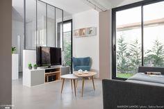 Les clients de cette jolie maison en plein cœur de Lyon, souhaitent aménager et décorer leur pièce de vie. Afin de créer un sas d'entrée plus intime, j'ai intégré une cloison type atelier en métal afin de garder le volume de l'espace intérieur et la transparence. De plus, la partie basse de cette nouvelle cloison a permis de placer le meuble de télévision face au canapé. Les meubles sur mesure viennent optimiser au maximum les espaces et offrent de nombreux rangements.