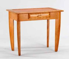 Leather Top Writing Desk. This modern heirloom writing desk is elegantly made from solid tiger maple hardwood. The desk top is inlaid with treated saddle leather. With a solid tiger maple frame along with solid tiger maple contoured legs, this desk will be a part of your family for generations.  The center drawer is fitted with a pull that is made from rare 2000 year old fossilized walrus ivory and carved antique Eskimo sled runner, which adds an eccentric charm to the piece. Saddle Leather, Writing Desk, Sled, Eccentric, Drawer, Hardwood, Ivory, Carving, The Originals