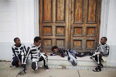 Young members of The North Side Skull and Bone Gang rest at a church doorway on Mardi Gras day in New Orleans, Louisiana, February 21, 2012.