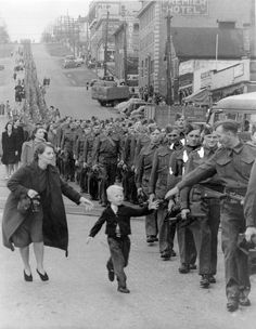 "Wait For Me Daddy,"" October 1, 1940: A line of soldiers march in British Columbia on their way to a waiting train as five-year-old Whitey Bernard tugs away from his mother's hand to reach out for his father."