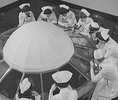 Cap-wearing students observing surgery through glass ceiling dome, 1942