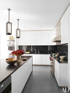 The kitchen is outfitted with Holly Hunt Studio pendant lamps, cabinetry by Piero Lissoni for Boffi, a granite backsplash and counters, a Wolf range, and a floor of leathered French limestone | http://archdigest.com