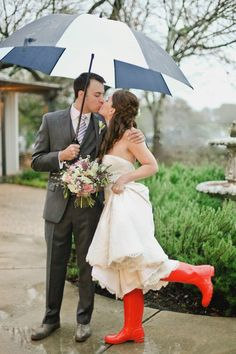 A rainy wedding day calls for bright boots and getting close under an umbrella. How cute! Find umbrellas for sale and/or rent at splendorforyourguests.com!  Splendor for Your Guests | Rental Company | Weddings | Events | Shawls | Blankets | Umbrellas | Parasols | Fans