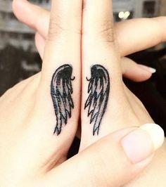Tatouages symétriques en forme d'ailes sur les index des deux mains