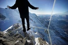Man stands on a glass floor of Chamonix Skywalk made of Pilkington Optiwhite™ on the Aiguille du Midi peak.