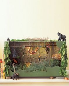 Kids can make a jungle by adding animal images out of magazines, rocks, grass, and sticks to a box.
