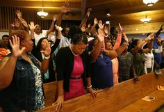 """Attendees chant """"Hands up, don't shoot"""" during a gathering with Michael Brown's family and Rev. Al Sharpton at the Greater St. Mark Missionary Baptist Church on Tuesday, Aug. 12, 2014, in Dellwood, Mo. The gathering at the church was in response to the police shooting of 18-year-old Michael Brown on Saturday. (Chris Lee/St. Louis Post-Dispatch/MCT)"""