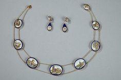 Demi-parure à micromosaiques comprenant un collier en or à sept médaillons ovales et double chaîne ainsi que des pendants d'oreilles en forme de goutte. <br/>Les micromosaiques sont incrustées dans des médaillons de verre bleu. Les boucles d'oreilles à pendants sont ornées des mêmes médaillons à micromosaiques. Chaque micromosaique décrit un monument de la Rome antique. <br/>Les parures à micromosaique sont apparues avec le développement du «Grand Tour» long v...