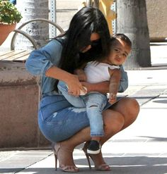 How Cute Is North West In Her Ripped Denim?/ THIS BABY GIRL IS GORGEOUS IN ANYTHING~ I JUST DON'T LOVE HER IN ALL BLACK, DOOM & GLOOM. SHE LOOKS ADORABLE HERE...EVEN THOUGH IT SEEMS THAT KK IS LITERALLY TWISTING THE CHILD'S LEG TO SIMPLY PUT THE CHILD'S SHOE BACK ON! C'MON KK~ EASY ON LITTLE NORI~ SHE'S A BEAUTIFUL LITTLE BABY DOLL BUT SHE' REAL!