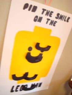 """Lego Party: Pin the Smile on the Lego Man. For this game, I just painted a face on a piece of foam board, and cut out a bunch of """"smiles"""" out of black card stock. The kids' names were written in white crayon on the front and they were stuck to the board using 3D glue dots."""