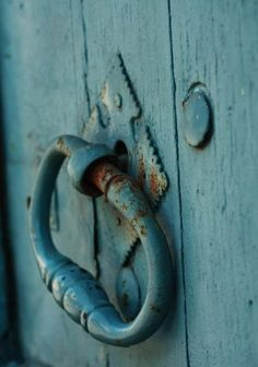 Rustic doorknobs on aged turquoise.