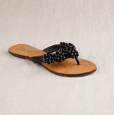 Simply sophisticated and perfectly practical, these comfortable flat sandals boast a sleek thong strap set with silver-tipped clusters of bauble beads. This glossed and polished pair with luxe soft insoles looks quite the pretty picture with any casual or dressy outfit this spring.