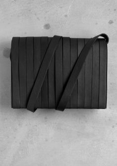 & OTHER STORIES A clutch made from soft leather covered with leather strips with a flap that fastens with two magnetic snaps.