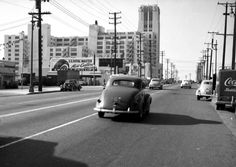 A view of the Boyle Heights Sears Roebuck, located at 2650 East Olympic Boulevard, looking from just east of Soto Street, showing the Shull & Phillips tire shop, a Foster and Kleiser billboard for United States Rubber Company tires, the Sears Building, and a Coca-Cola delivery truck (1950)