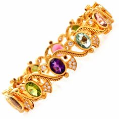 This exquisite vintage multi-gem bangle bracelet of artistic design and immaculate artisanship is handcrafted in solid 18K yellow gold, weighing approx. 54.3 grams and measuring 7.5″ around the wrist. This vivacious vintage bracelet of unsurpassed feminine grace incorporates romantically designed scrolls, embellished with 'twisted rope' textured gold, complemented by diamond-encrusted crown and paisley motif profiles. A number of 12 oval-faceted gemstones, consisting of one amethyst, two…