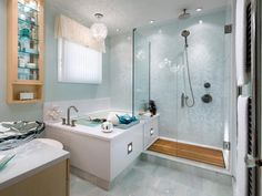 Cool, clean colors, modern fixtures and smart yet stylish storage combine to create a refreshing, luxurious bathroom. The frameless glass enclosure of the walk-in shower keeps the space light and airy while separating it from the deep soaker tub.