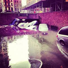 Rising water rushes into a subterranian parking garage in the Financial district.