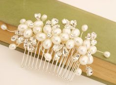 Lustrous ivory pearl bridal hair comb. This pretty flower hair accessory is an elegant finishing touch to wedding day hair.    Featuring ivory