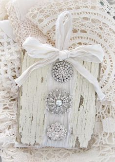 An old piece of barn wood adorned with white ribbon and vintage rhinestone brooches