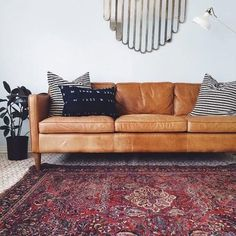 camel leather sofa with rich traditional rug and modern mirror