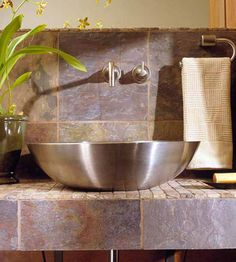 This ultra-modern sink truly stands out among stunning stone tiles. A contemporary stainless-steel faucet fits in perfectly with the vessel sink. The reflective surface of the sink helps to bring a little extra shine to the bathroom./
