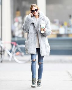 Olivia Palermo wears a neutral sweater, shearling peacoat, skinny jeans, and high-top sneakers