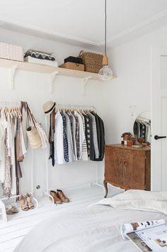 Open closet in a bright bedroom