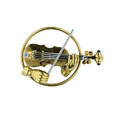 18K yellow and white gold Tiffany & Co circular pin depicting a violin being played with white gold strings and bow set with one round brilliant cut diamond (.05 carat) and two cabochon sapphires set in the scroll, circa 1950s.
