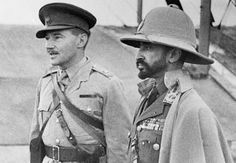 Haile Selassie (right), exiled Emperor of Ethiopia, whose empire was absorbed by Italy, returns with an Ethiopian army recruited to aid the British in Africa, on February 19, 1941. Here, the emperor inspects an airport, an interpreter at his side. On May 5, 1941, after the Italians in Ethiopia were defeated by Allied troops, Selassie returned to Addis Ababa, and resumed his position as ruler.