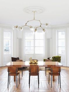 Dining space with architectural detailing, a modern chandelier, and Jean Prouvé dining chairs